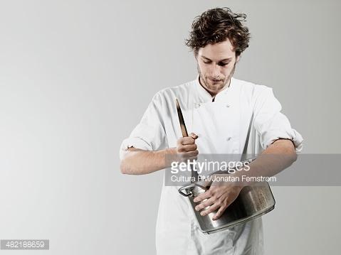Homem cozinhando panela de alumínio com colher