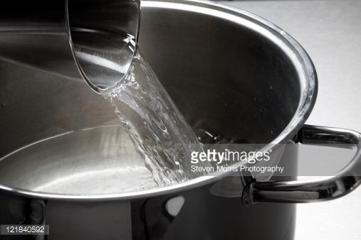 derramando água na panela de alumínio