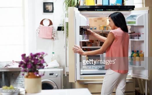 mulher olhando geladeira