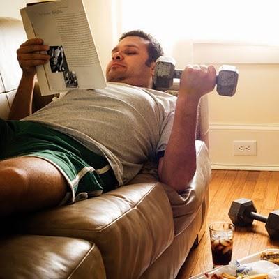 homem preguiçoso no sofá treinando com halteres